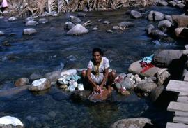 Woman crouching on a rock washing clothes in a river