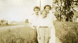 [Three unknown young women standing on a path with high grass on either side]