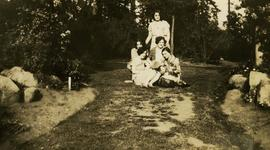 [Unidentified adolescent girls posing on a grass path]