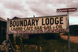 "Sign for ""Boundary Lodge"" as well as ""70 miles to Dawson"""