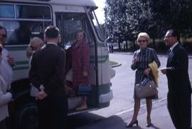 Group of people standing by a bus