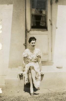 [Unidentified woman sitting on steps]