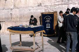 Books on a table with a blue table cloth, as well as a hanging blue cloth with Hebrew writing on ...
