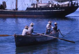 Four men sitting in a boat with one man rowing and a ship in the background