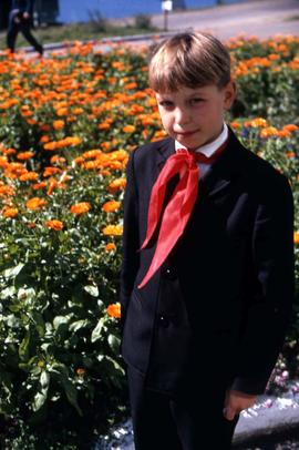 Unidentified boy standing in front of a flower bed wearing a red scarf