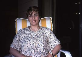 Unknown woman sitting on a yellow and white stripped chair