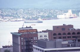 Buildings on West Hastings Street in Vancouver in the foreground, and Vancouver Harbour with ship...