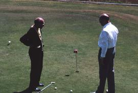 Two unknown men standing on a golf course green with a putter and golf balls