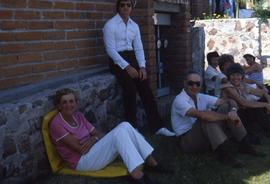 Seven unknown people sitting on the ground next to a brick wall posing for the camera