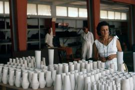 Phyliss Snider looking at a display of vases inside a building, possibly a factory