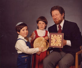Robert Edel with two children, holding matzah clock