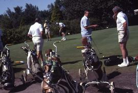 Golf push carts in the foreground and five golfers on a putting range in the background