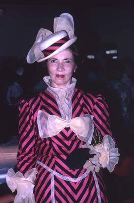 Unknown woman wearing a black and pink dress with matching straw hat
