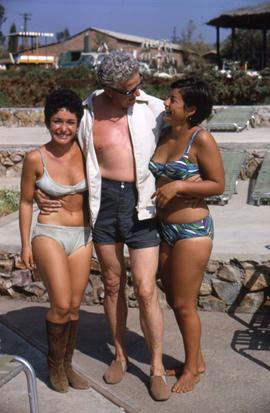 Two unknown women and an unknown man in their bathing suits posing for the camera
