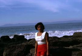Phyliss Snider posing for the camera in front of rocks and a body of water