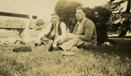 [Ben Dayson and an unidentified man sitting in a park]