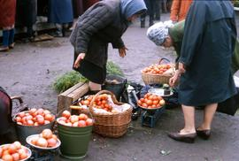 Woman selling a batch of tomatoes to another woman in a street market
