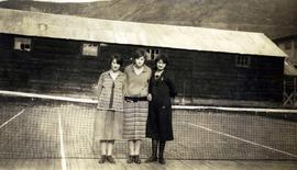 [Three unknown young women posing in front of a tennis net on a tennis court]