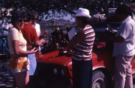 Unknown people standing around a red truck