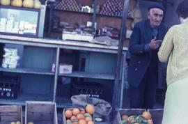 Unidentified man, standing behind crates of oranges, speaking with an unidentified woman