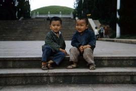 Two children sitting on stairs