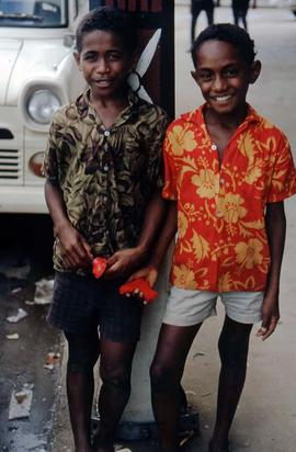 Two boys standing on a street corner