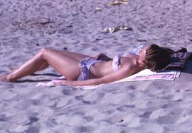 Woman in a bikini sun tanning while laying on sand