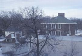 Winter scene with several buildings including a red building with a green roof in the background on the right and a tree in the foreground
