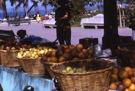 Table with baskets of fruits on it and a person in the shade in the background