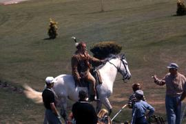 Unknown man, wearing First Nations style clothing, on a white horse with people standing around t...