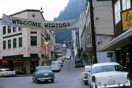 "Street in Juneau, Alaska with a ""Welcome Visitors"" banner hung across it"