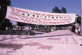 White cloth banner hung over a sidewalk with a Spanish sentence painted in red