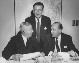 Three men, two seated at table, one standing