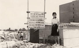 Woman standing beside Hadassah-WIZO sign at a construction site for a day creche