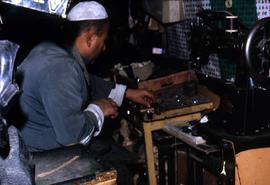 Unidentified man working next to a sewing machine