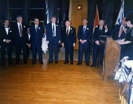 60th anniversary [- group of men lined up and an unknown woman is standing at a podium on the far...