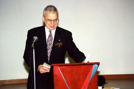 [Bernie Simpson at a red podium for the Opening Collingwood Project]