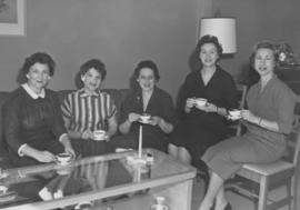 Women seated around coffee table