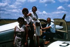 Phyliss Snider, two unidentified women and an unidentified man standing in front of an airplane