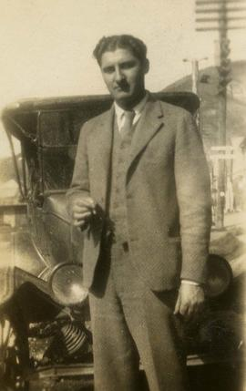 [Dr. Robert Franks holding a cigarette and posing in front of a car]