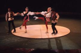 Four circus performers on roller-skates in a circus ring