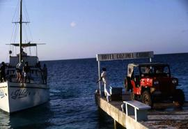 "Red jeep parked at the end of a dock with a sign over the jeep that reads: ""Hotel Cozumel Ca..."