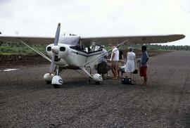 Group of people standing on a gravel runway either waiting to board or exit a small airplane