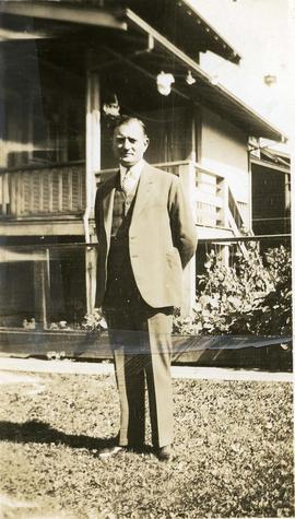 Charlie Nemetz [standing in front of a house]