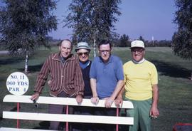 Four unknown men posing behind a bench on a golfcourse