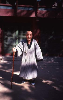 Elderly man with a cane in front of a building