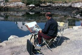 Unknown man with his back to the camera painting on a rocky shoreline with water in front of him