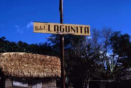 "Sign that reads: ""Hotel Lagunita"" with a small building with a thatched roof"