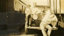 [Two men, a woman and a child posing on the front of a car]