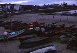 Colourful boats lined up on a beach with people standing around the boats and people on the beach...